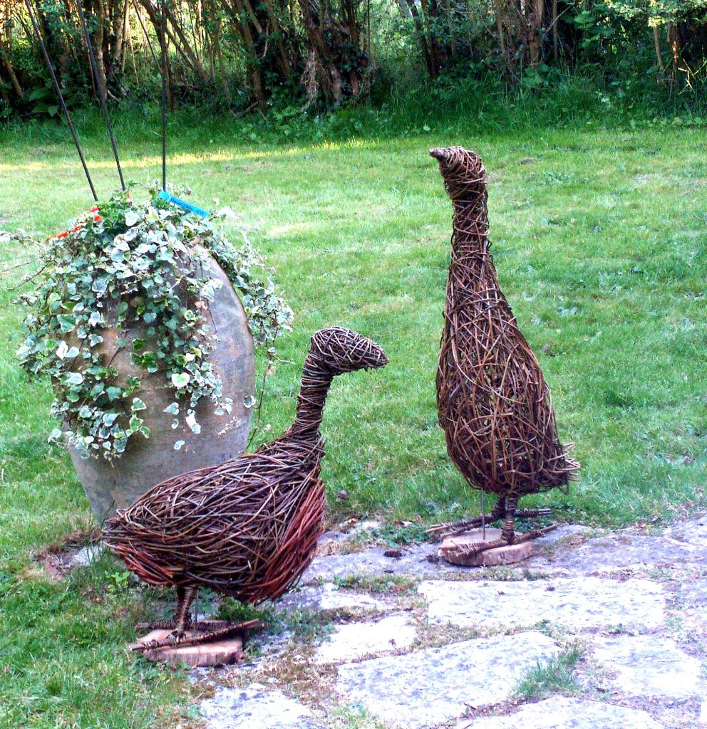 willow goose and willoe duck willow sculptures in a garden standing by a large planted urn by Jacqueline Rolls