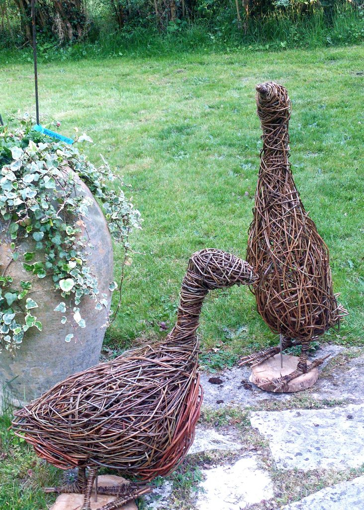 Photo of willow sculpture duck and goose made using multi color mix of brown willow the duck has a rusty underbelly