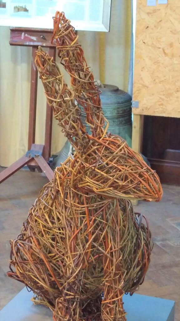 willow hare sculpture sitting on a plinth , paws in front and ears up he is facing to one side
