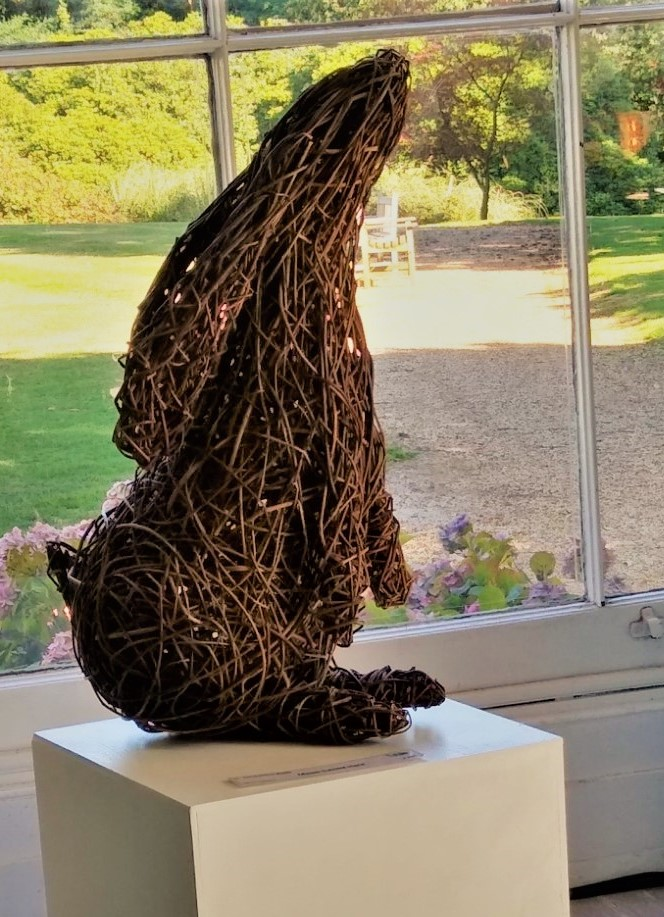 Moon gazing willow sculpture sitting in front of a window with garden behind