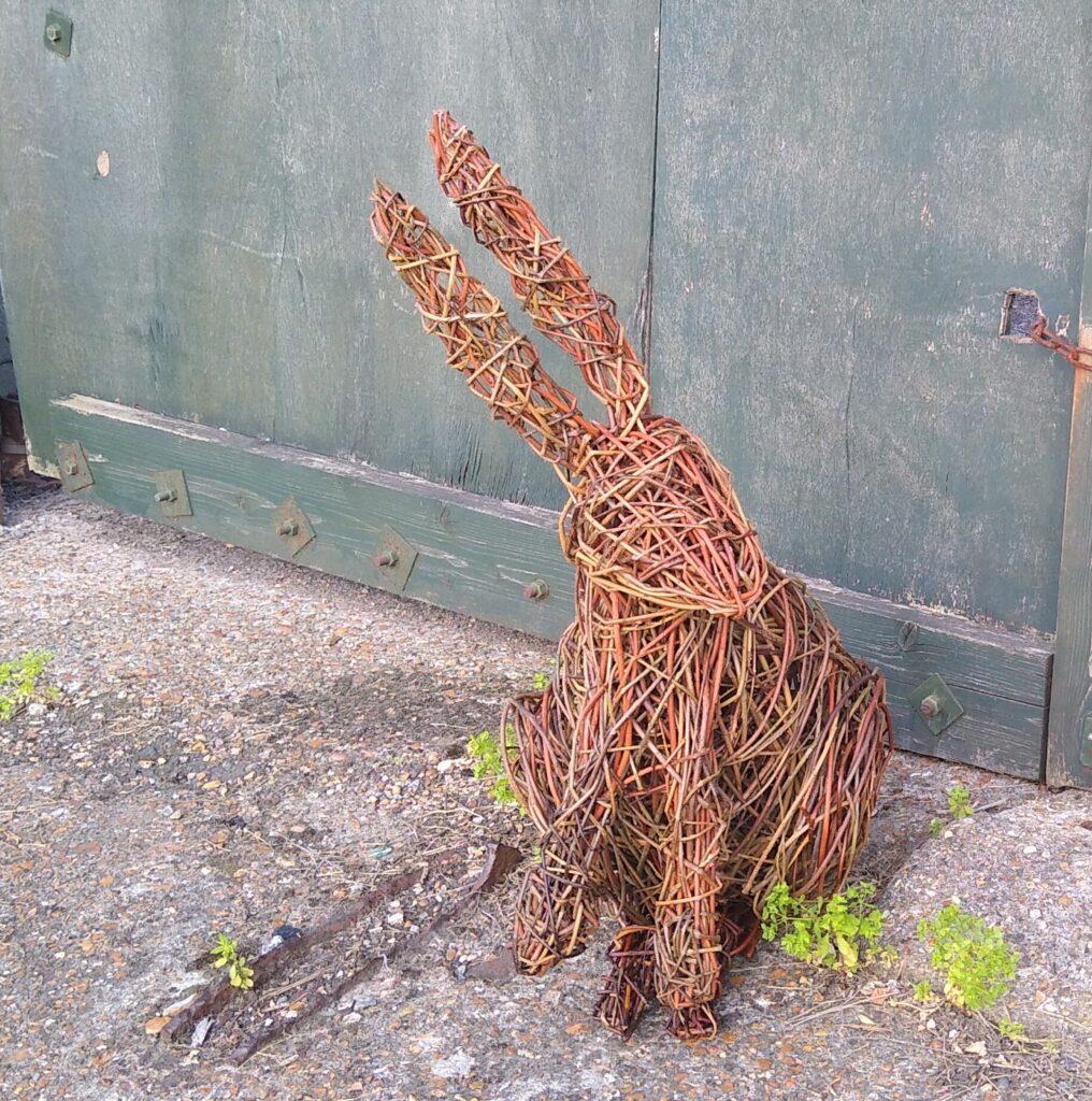 willow hare sculpture sitting on pavement in front of wooden door weeds growing through cracked pavement, door has dark green mottled paint