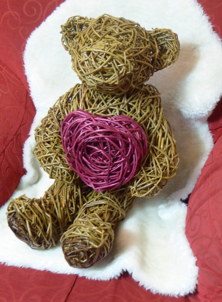 teddy bear willowsculpture sitting on seat with sheepsking blanket