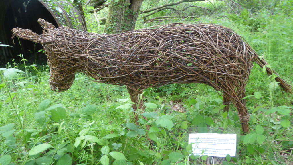 Donkey willow sculpture in woods viewed from the side