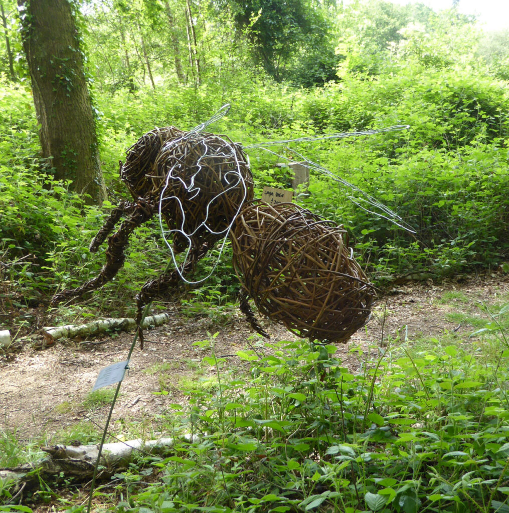 Large willow honey bee sculpture in woods seen from back view showing metal wire wings