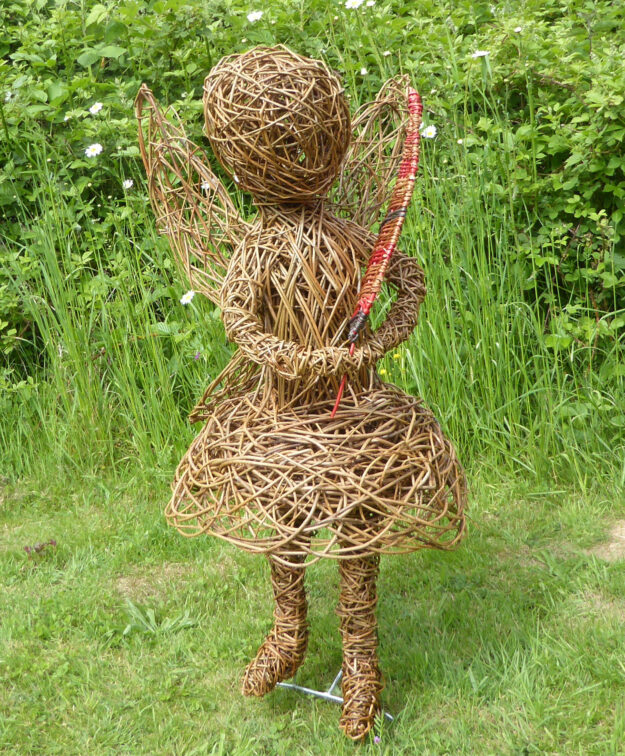 fairy willow sculpture child holding leaf large standing in meadow