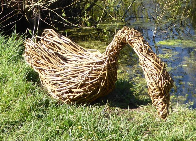 Willow sculpture of a swan sitting on the grass next to a pond neck outstretched